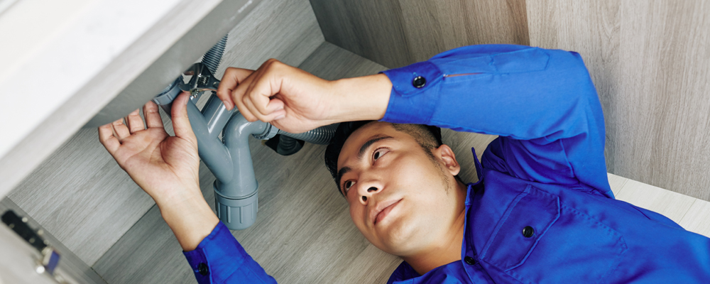 Handome young Asian plumber installing new pipes under kitchen sink