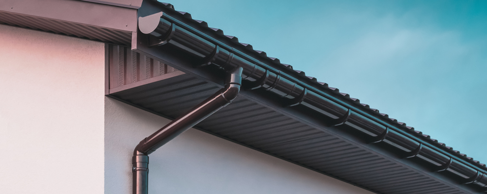 Chocolate-colored plastic gutter on the roof of the building and downpipe on the wall.