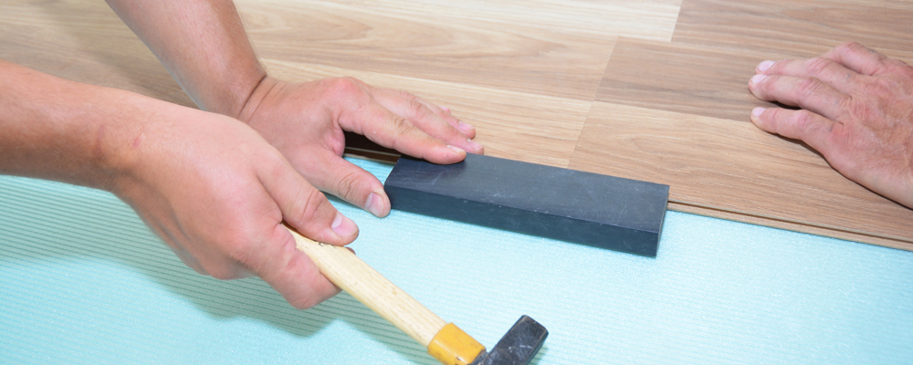 Contractors installing wooden laminate flooring with insulation and soundproofing sheets. Man laying laminate flooring. Man laying laminate flooring.