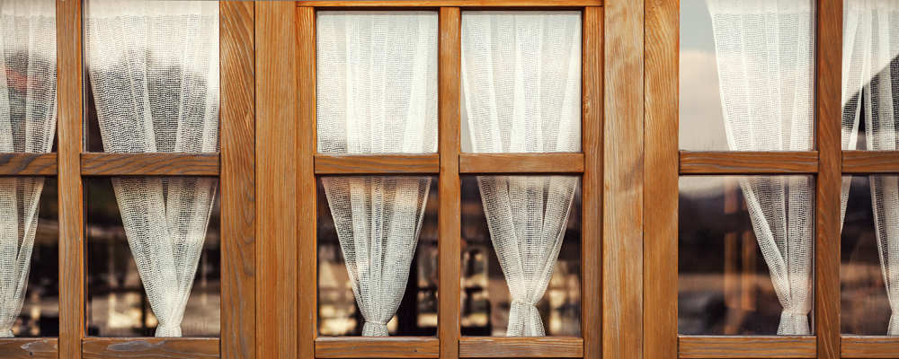 Wooden decorative windows with old fashioned white curtains.