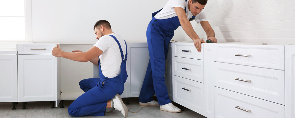 Maintenance workers installing new kitchen furniture indoors