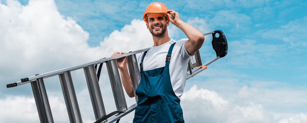 panoramic shot of cheerful repairman holding ladder and smiling against blue sky with clouds