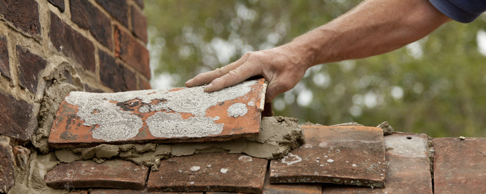 A tiler sliding a clay ridge tile into position on a bed of cement. Roof being restored on a period property. Tiles are over 200 years old.