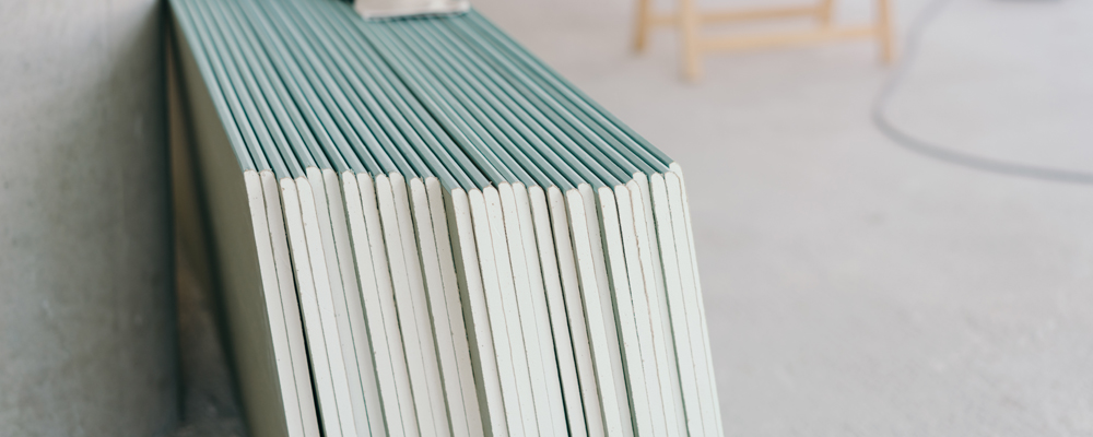 White chip board stacked against the wall inside a new build house with work table visible in the background in a spacious room