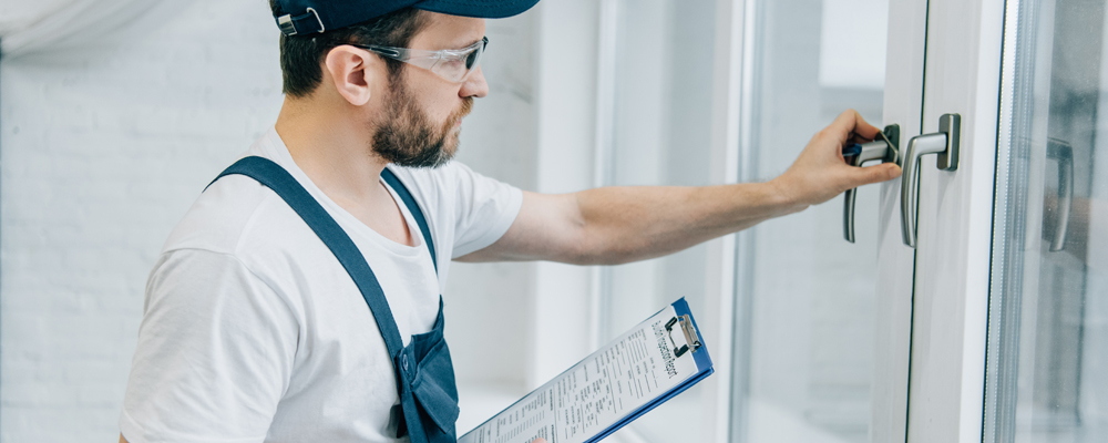 handyman in goggles holding clipboard and checking window handle